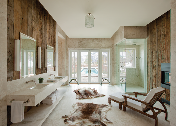 The master bath includes reindeer hide rugs by Pologeorgis Furs, a teak chair and ottoman covered in Ralph Lauren white terrycloth and contemporary sconces by Jean Perzel.