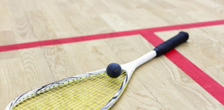 A squash racquet on the floor of a court with a ball on top.
