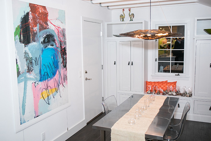 A clear kitchen table with modern artwork hung on the wall