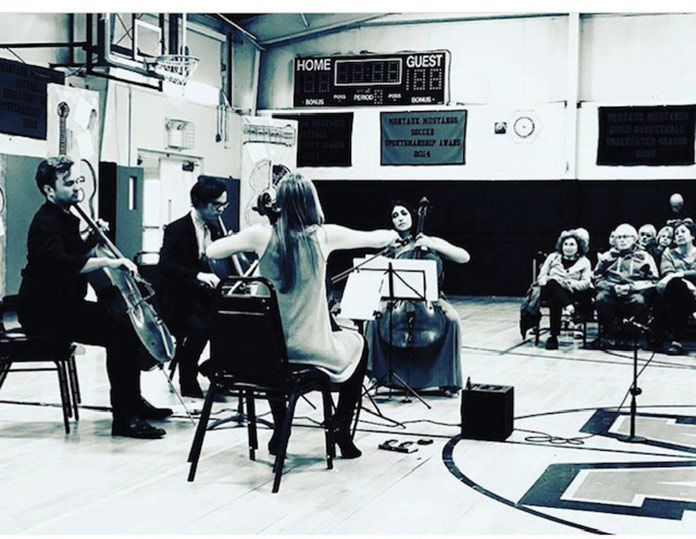 Black and white image of students playing intruments in an auditorium